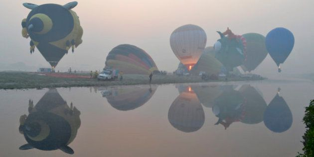 Hot air balloons are reflected on the water of the Yamuna River on a misty morning on the second day...