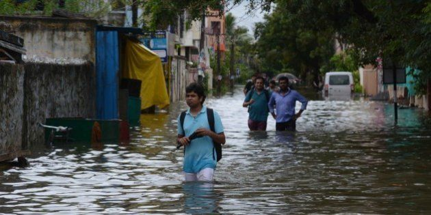 Indian people make their way on a flooded street following heavy rain in Chennai on November 16, 2015....