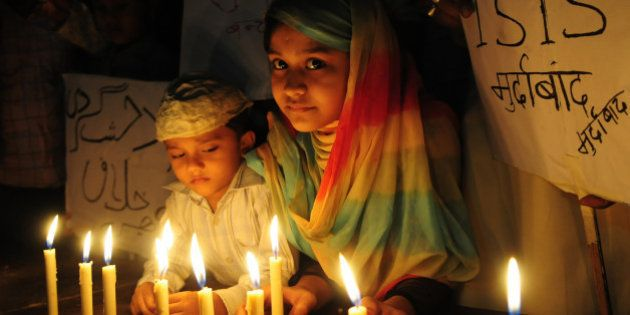 BHOPAL, INDIA - NOVEMBER 15: Muslim kids hold placard with slogans against the ISIS during a candle light...