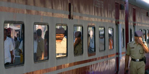 Kolkata, INDIA: Indian policemen are reflected in a train carriage windows as they walk past the high...