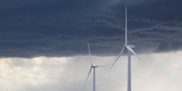 FILE - This Sept. 27, 2012 file photo, shows electricity-generating wind turbines in a corn field just...