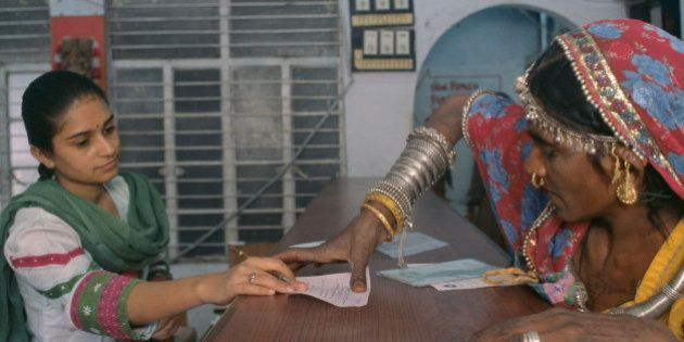 Rural Woman Putting A Thumb Impression In A Bank To Open Her Bank Account At Bank, Ahmedabad,India. (Photo...