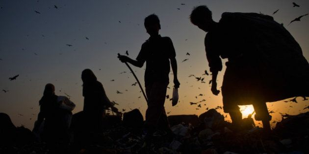NEW DELHI, INDIA - FEBRUARY 18: Indian workers called Rag Pickers, sort through garbage and pick out...