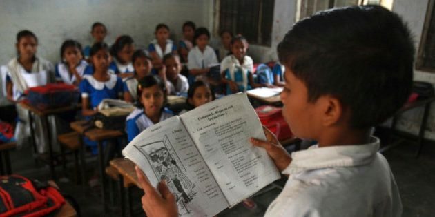 A Bangladeshi student reads as others listen during English lessons at a government run primary school...