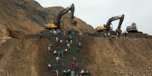 In this June 15, 2015 photo, freelance jade miners collect jade stones in an earth dump of a companies'...