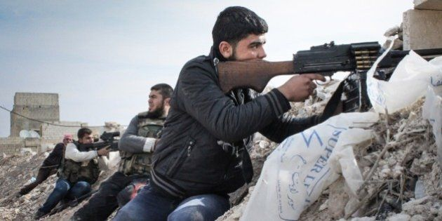 Free Syrian Army rebels take up positions along an embankment on the outskirts of the northwestern city...