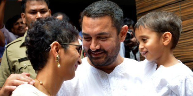 Indian Bollywood actor Aamir Khan, (C), with his wife, director Kiran Rao and son Azad celebrates and wishes his fans Ramzan Eid Mubarak at his residence in Mumbai on July 18, 2015.  AFP PHOTO        (Photo credit should read STR/AFP/Getty Images)