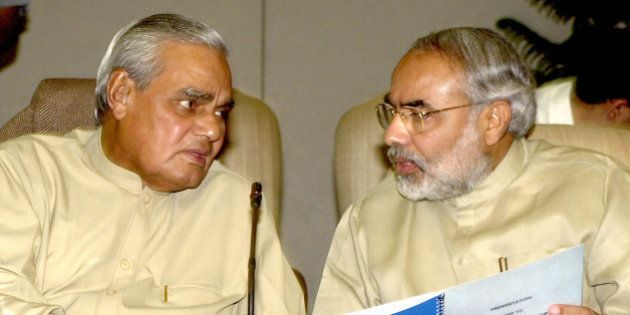 Indian Prime Minister Atal Bihari Vajpayee, left, speaks with Gujarat Chief Minister Narendra Modi at...
