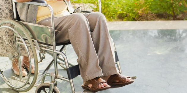 Senior man with hands clasped in wheelchair