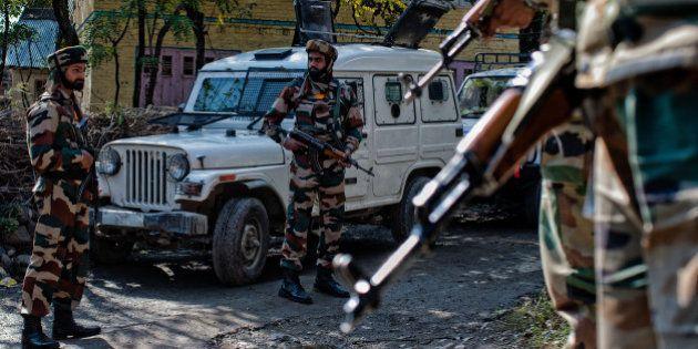 BONGAM, KASHMIR, INDIA - OCTOBER 21: Indian government forces stand guard during a gun battle between...