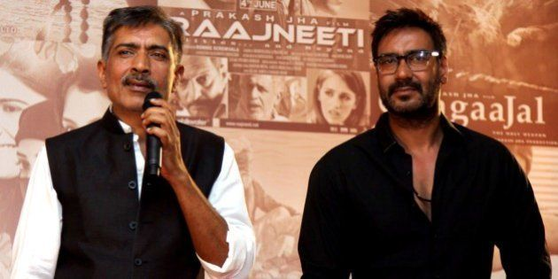 Indian Bollywood actor Ajay Devgn (R) poses for a photograph during a promotional event for new films...