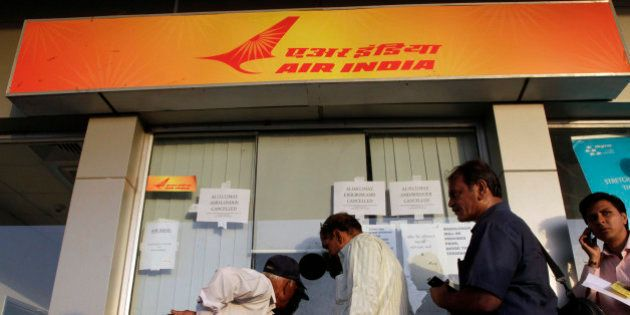 Indian passengers stand in a queue to make enquiries at an Air India counter at the airport in Ahmadabad,...
