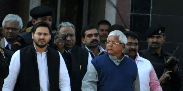 Indian politician Lalu Prasad Yadav (R) walks with his son Tejaswi (L) and security personnel as he leaves...