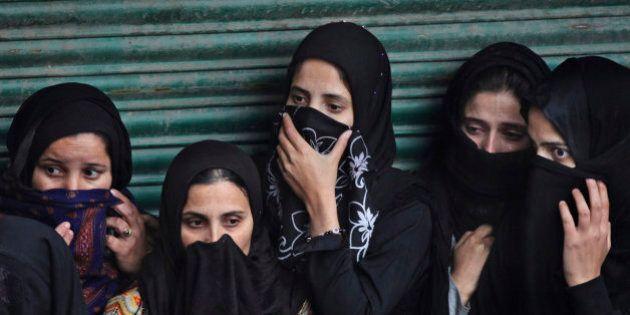 Kashmiri Shiite Muslim women watch an Ashoura procession in Srinagar, Indian controlled Kashmir, Saturday,...
