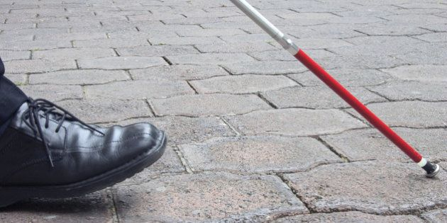 Close-Up of Blind Man's Black Shoe and White Cane