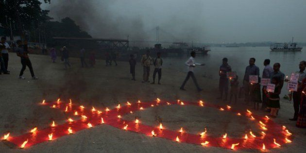 Indian social activists and children light a World AIDS Day awareness sign in Kolkata on December 1,...