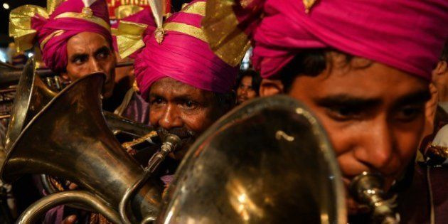Members of an Indian wedding band play brass instruments during a religious procession for the Hindu...