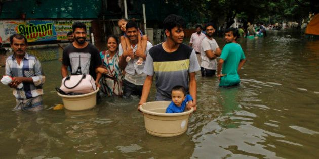 People with their children wade through flood waters in Chennai, India, Thursday, Dec. 3, 2015. The heaviest...
