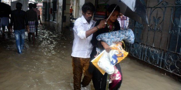 An Indian couple shelter under an umbrella as they walk with their child through floodwaters inundating...