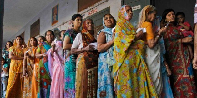 Indian women stand in queue to cast their votes for the second phase of Gujarat state assembly elections...