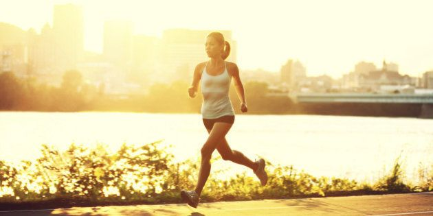 female runner running at sunset in city park. Healthy fitness xwoman jogging outdoors. Montreal skyline...