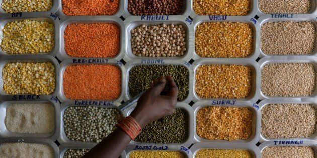 An Indian shopper examines pulses and food grains at a shop at the Agricultural Produce Marketting Committee...