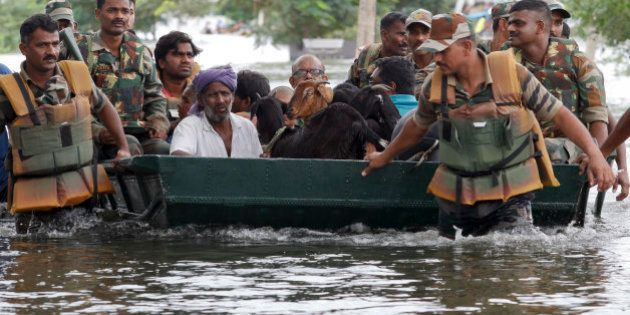 Residents and their goats are rescued by Indian army soldiers from a residential area flooded following...