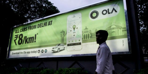A pedestrian walks past an advertisement for the Ola ride-hailing service and application, owned by ANI...