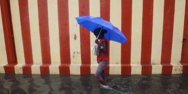 An Indian girl walks under an umbrella along a waterlogged street following heavy rain in Chennai on...
