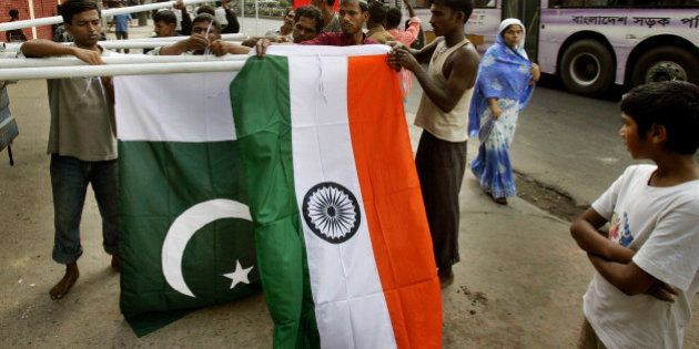 Workers erect national flags of India, front, and Pakistan as pedestrians look on in preparations for...