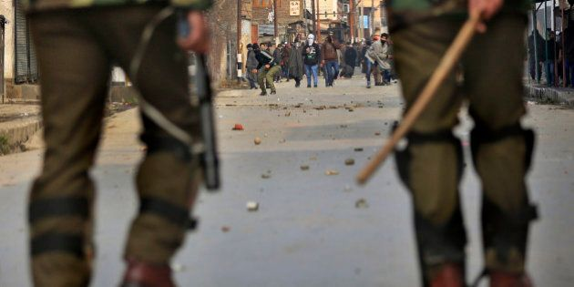 Masked Kashmiri protesters throw stones and bricks at Indian police during a strike in Srinagar, India,...