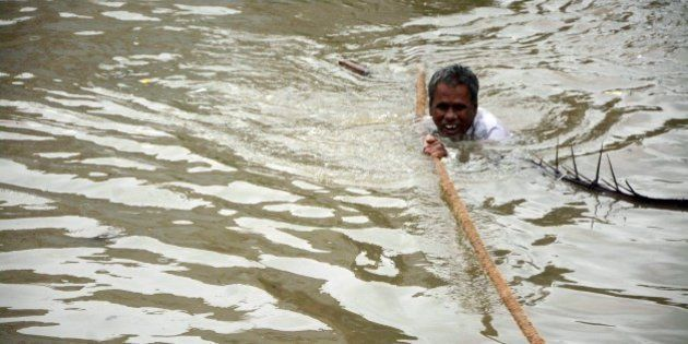 TOPSHOT - An Indian man clings to a rope as he makes his way through floodwaters in Chennai on December...