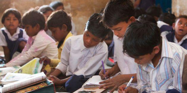 Indian schoolchildren doing their schoolwork in the classroom at their poor village school outside Bandhavgarh...
