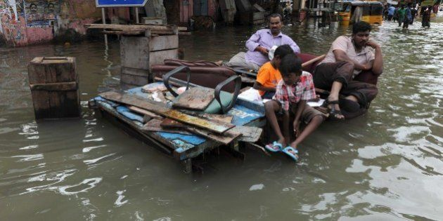 Indian residents sit on wooden pallets in floodwaters in Chennai on December 3, 2015. Thousands of rescuers...