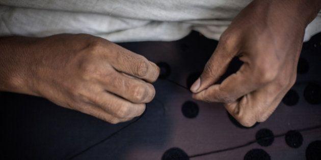 Sahil Ahmed embroiders a delicate fabric at fashion designer Anjana Das' workshop in Shahpur Jat village...