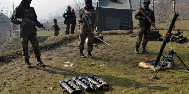 Indian army soldiers prepare to fire mortar shells towards hiding suspected militants in the Maniga area...