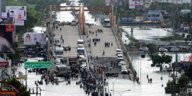 Indian residents and motorists gather on a flyover as others wade through floodwaters in Chennai on December...