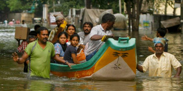 Volunteers rescue flood affected people on a country boat from a residential area in Chennai, India,...