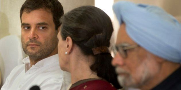 India's outgoing prime minister Manmohan Singh, sits on the right as Congress party president Sonia...