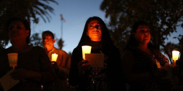 SAN BERNARDINO, CA - DECEMBER 07: People hold candles as they attend a vigil held at the San Bernardino...