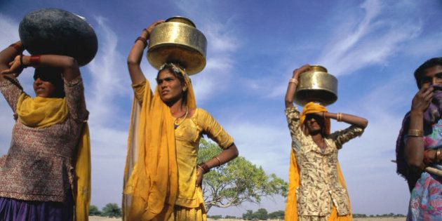 India, Rajasthan, three tribeswomen collecting water in brass