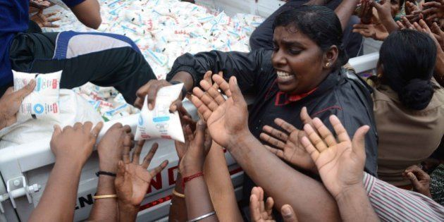 Indian volunteers distribute packets of milk from the back of a vehicle to flood affected residents in...