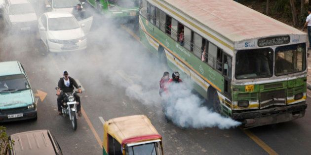 Smoke comes out of a public bus waiting at a traffic light in New Delhi, India, on Saturday, Nov. 26,...