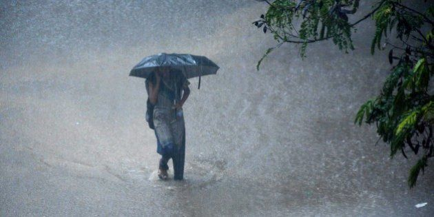 A young Indian woman walks under an umbrella through floodwaters in Chennai on December 1, 2015, during...