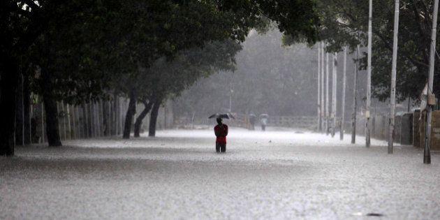 TOPSHOT - An Indian man shelters under an umbrella as he walks through floodwaters in Chennai on December...