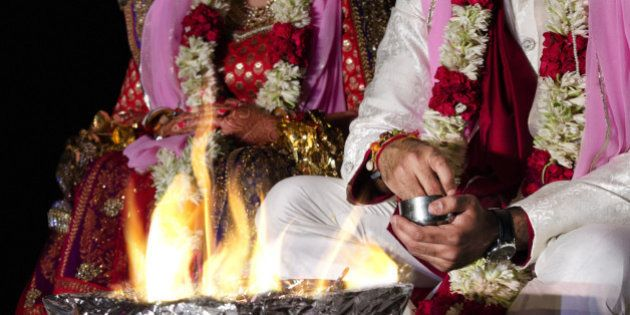 An Indian couple worshipping the fire deity, as a part of the Indian traditional wedding rituals.Fire...