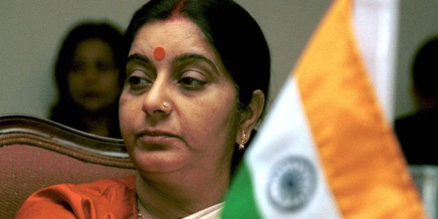 India's Broadcast Minister Sushma Swaraj sits behind an Indian flag as she attends a session of the Information...