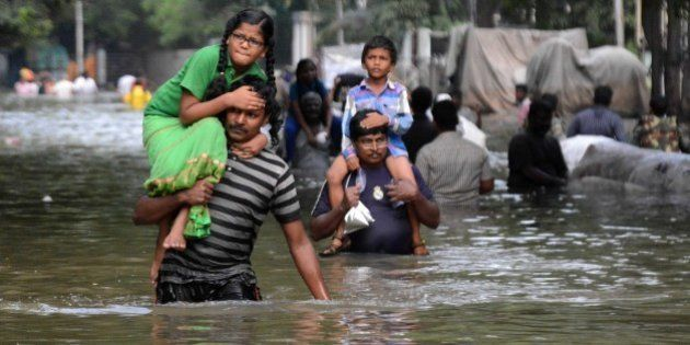 Indian residents carry children as they walk through floodwaters in Chennai on December 3, 2015. Thousands...