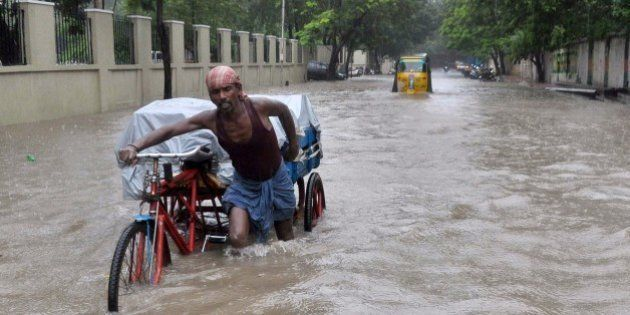 An Indian labourer pushes his cycle trishaw through floodwaters in Chennai on December 1, 2015, during...