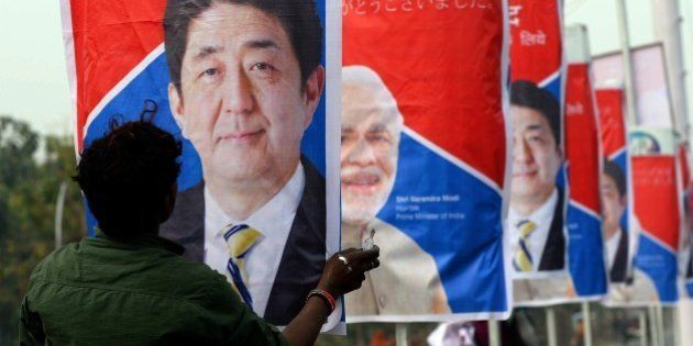 An Indian worker hangs posters of Japan's Prime Minister Shinzo Abe (L) and India's Prime Minister Narendra...